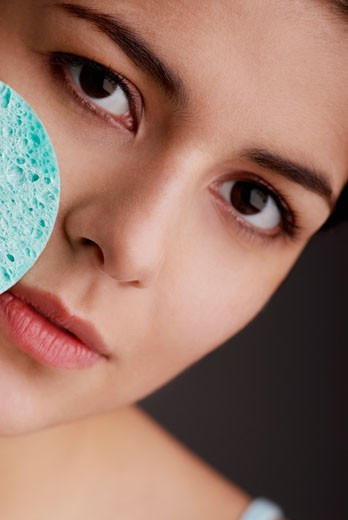 Portrait of a young woman scrubbing her face with a sponge : Stock Photo
