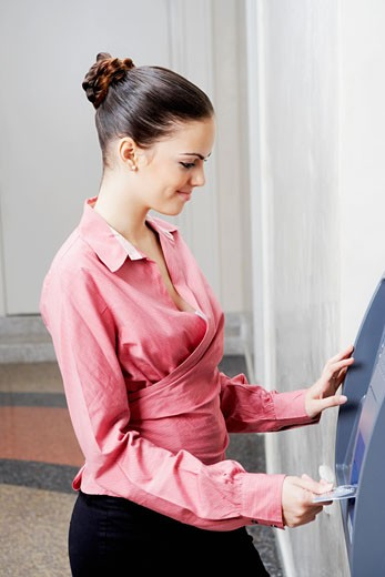Side profile of a businesswoman inserting a credit card into an ATM : Stock Photo