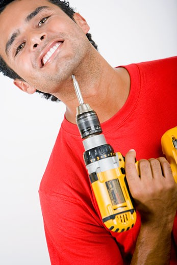 Portrait of a young man holding a drill machine under his chin : Stock Photo