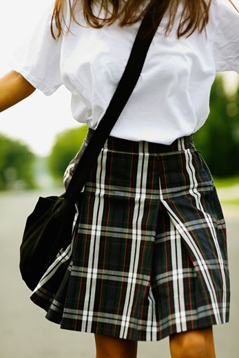 Stock Photo: 1663R-17986 Mid section view of a schoolgirl walking on the road