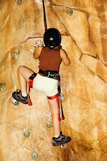 Rear view of a girl climbing a wall : Stock Photo