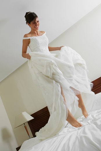 Low angle view of a bride jumping on the bed : Stock Photo