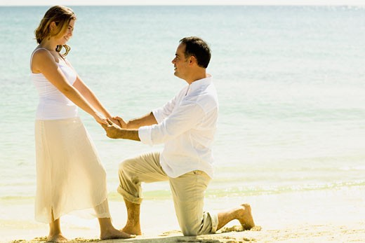 Side profile of a mid adult man kneeling in front of a young woman on the beach : Stock Photo