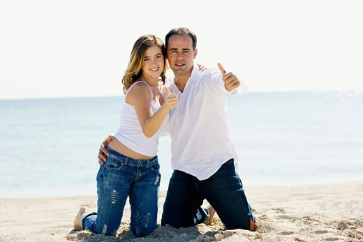 Portrait of a mid adult man and a young woman kneeling on the beach and showing Thumbs Up sign : Stock Photo
