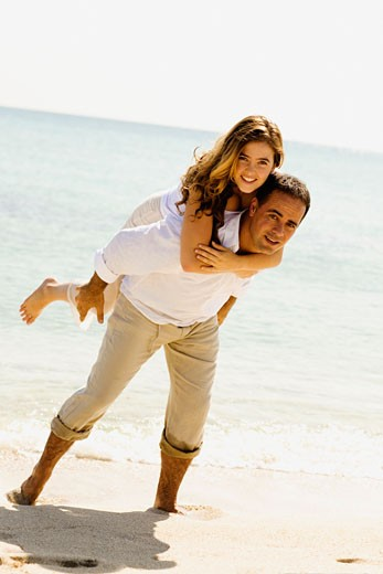 Portrait of a young woman riding piggyback on a mid adult man on the beach : Stock Photo