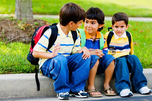 Three schoolboys sitting together : Stock Photo