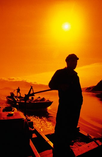 Silhouette of a man standing on a motorboat, Yarlung Tsangpo River, Tibet, China : Stock Photo