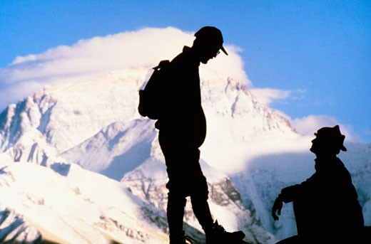 Stock Photo: 1663R-18623 Silhouette of two men on a mountain with snow covered mountains in the background, Mt Everest, Tibet, China