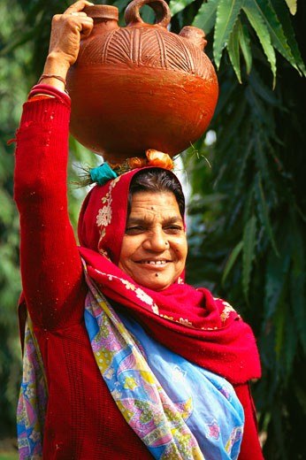 Close-up of a mature woman carrying a pot on her head and smiling : Stock Photo