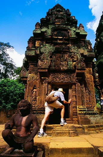 Stock Photo: 1663R-19118 Rear view of a man peeking into a temple, Banteay Srei, Angkor, Siem Reap, Cambodia