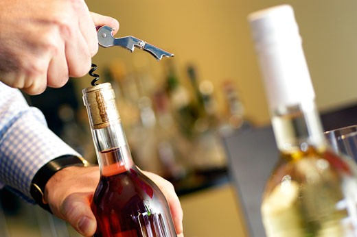 Close-up of a man unscrewing cork of a wine bottle : Stock Photo
