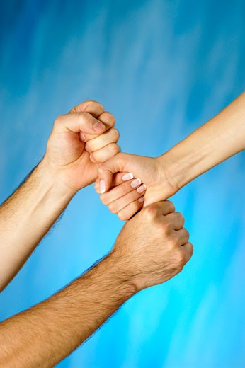 Close-up of a man and a woman's hands stacking fists : Stock Photo