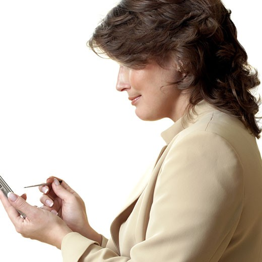 Side profile of a businesswoman using a personal data assistant : Stock Photo