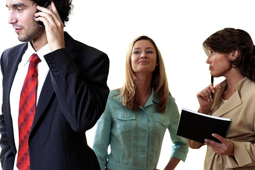 Stock Photo: 1663R-20362 Businessman talking on a mobile phone with his two secretaries standing behind him