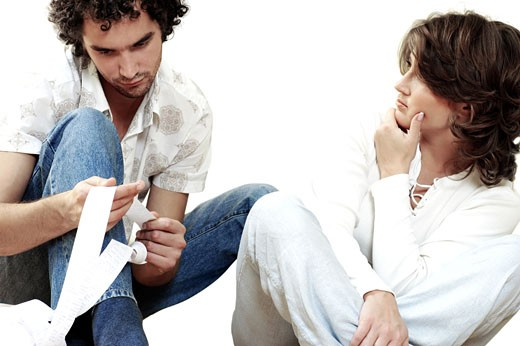 Young man sitting with a young woman holding a receipt : Stock Photo