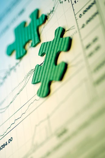 Jigsaw pieces on a stock market report : Stock Photo