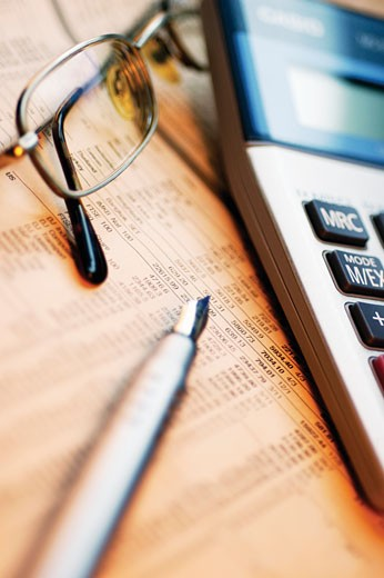 Close-up of a pen with eyeglasses and a calculator on a financial newspaper : Stock Photo
