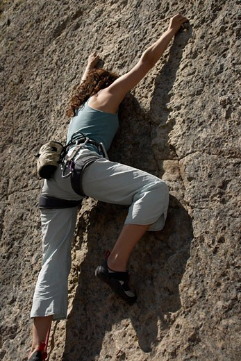 Female rock climber scaling a rock face : Stock Photo