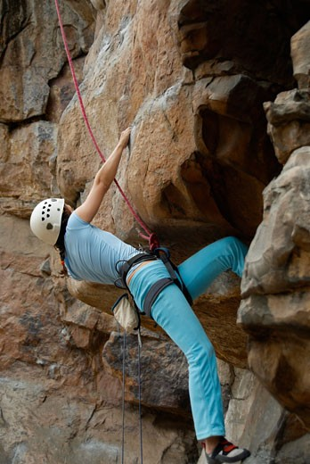 Low angle view of a female climber ascending a steep rock : Stock Photo