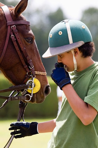 Stock Photo: 1663R-21443 Teenage boy standing with a horse