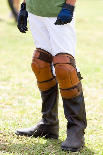Low section view of a teenage boy wearing riding boots and kneepads : Stock Photo
