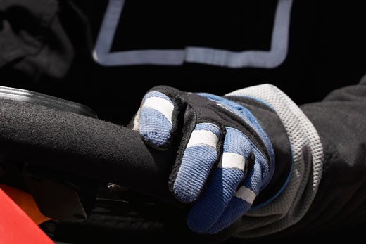 Close-up of a person's hand on the steering wheel of a racecar : Stock Photo