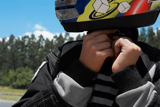 Close-up of a person adjusting his crash helmet : Stock Photo