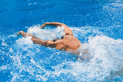 Stock Photo: 1663R-21721 Rear view of a man swimming the butterfly stroke in a swimming pool