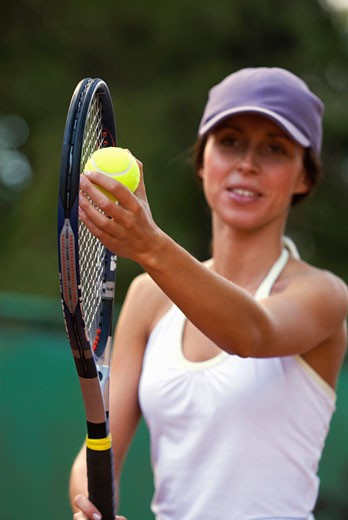 Close-up of a young woman holding a tennis ball and a tennis racket : Stock Photo