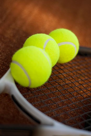 Stock Photo: 1663R-21781 Close-up of three tennis balls on a tennis racket