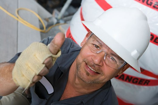 Portrait of a male construction worker showing a thumbs up sign and smiling : Stock Photo