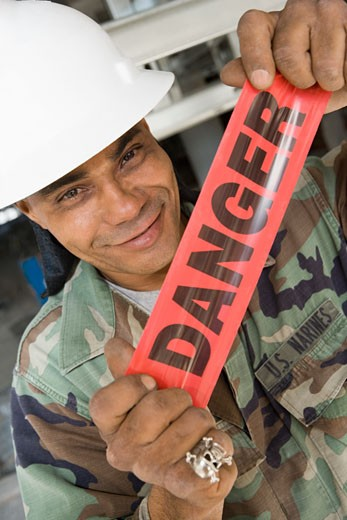 Stock Photo: 1663R-23290 Portrait of a male construction worker holding a cordon tape and smirking