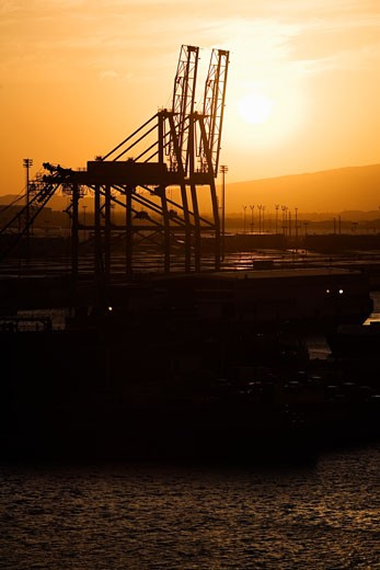 Stock Photo: 1663R-23560 Silhouette of cranes at a commercial dock