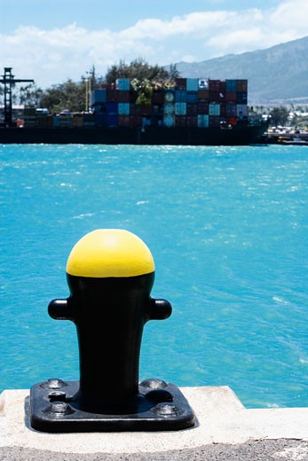 Stock Photo: 1663R-23562 Close-up of a bollard with cargo containers in the background at a commercial dock