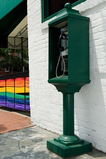 Pay phone near a building with the rainbow flag in the background : Stock Photo