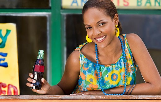 Portrait of a young woman leaning on a railing and holding a cola bottle : Stock Photo