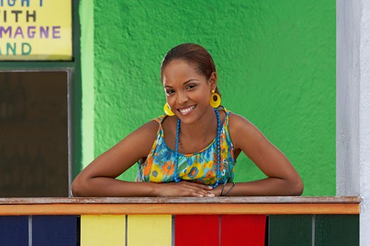 Stock Photo: 1663R-23976 Portrait of a young woman leaning on a railing and smiling