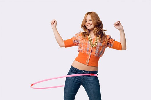 Portrait of a young woman playing with a hula hoop : Stock Photo
