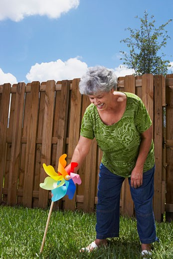 Stock Photo: 1663R-24321 Senior woman holding a pinwheel in a backyard and smiling