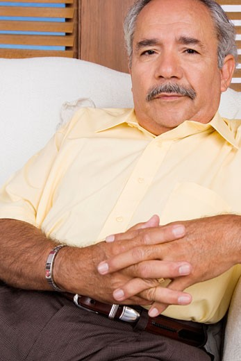 Stock Photo: 1663R-24324 Portrait of a senior man sitting on a couch with his hands clasped