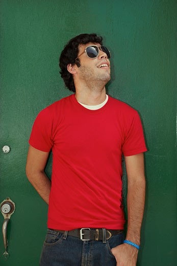 Stock Photo: 1663R-24414 Young man standing in front of a closed door and wearing sunglasses