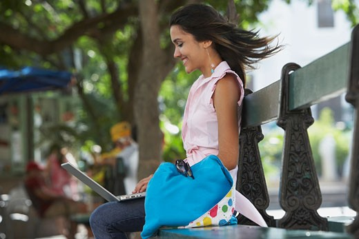 Side profile of a young woman sitting in a park and using a laptop, Old San Juan, San Juan, Puerto Rico : Stock Photo