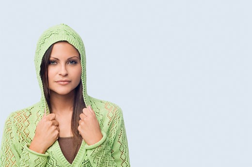 Portrait of a young woman holding collars of her hooded shirt : Stock Photo