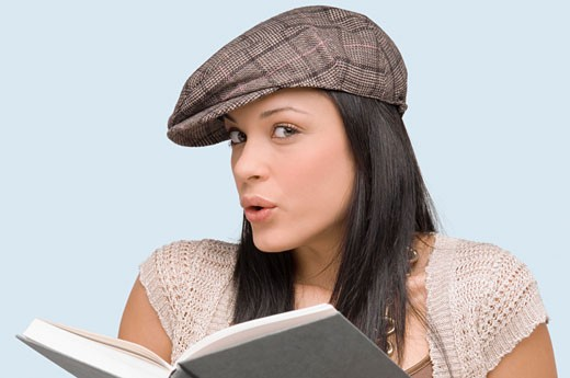 Stock Photo: 1663R-24809 Portrait of a young woman whistling with a book in front of her