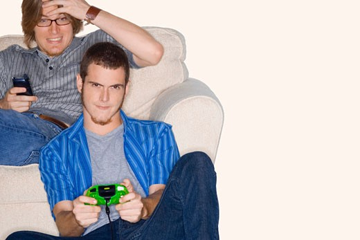 Young man playing video game with another young man using a mobile phone behind him : Stock Photo