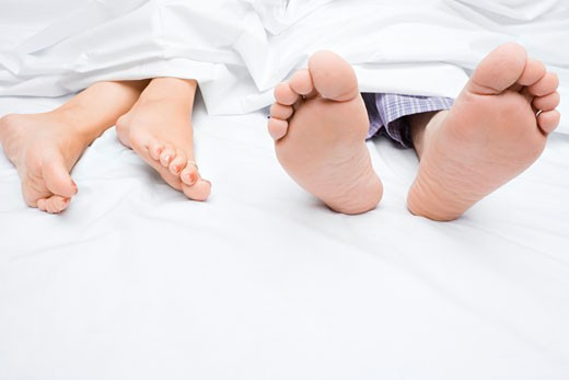Stock Photo: 1663R-24884 Close-up of a couple's feet on the bed