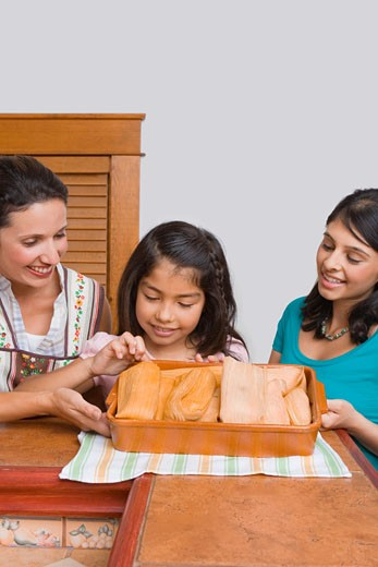 Mid adult woman with her two daughters smiling with a tray of breads in the kitchen : Stock Photo