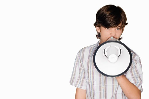 Portrait of a teenage boy blowing a bullhorn : Stock Photo