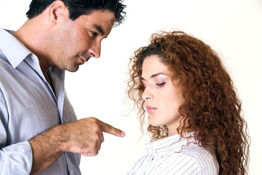 Side profile of a mid adult man pointing to a young woman : Stock Photo