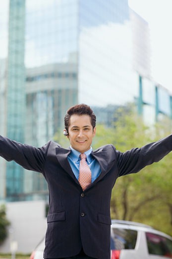 Stock Photo: 1663R-26136 Portrait of a businessman standing with his arms outstretched and smiling
